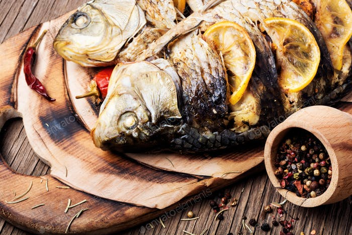 Grilled fish with potato and lemon on wooden table
