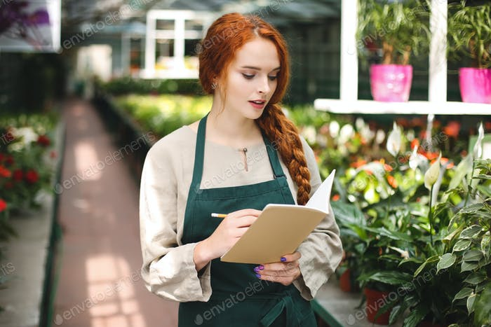 Young florist in apron standing with pencil in hand and thoughtfully writing in notepad