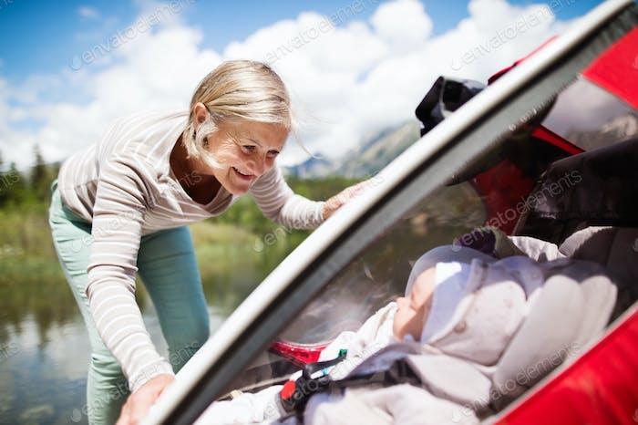 Senior woman and grandchildren in jogging stroller.