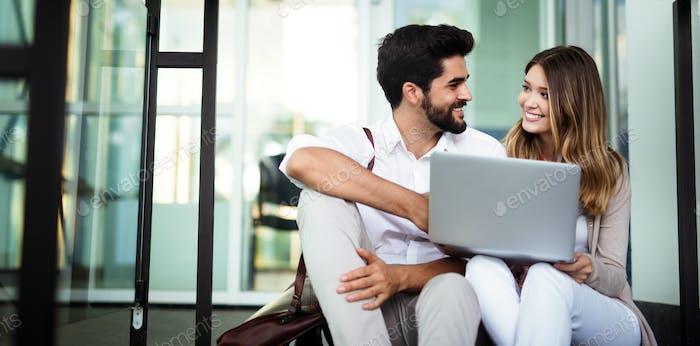Schöne junge Geschäftsfrau und gutaussehende Geschäftsmann mit einem Laptop, sprechen und lächelnd auf Pause
