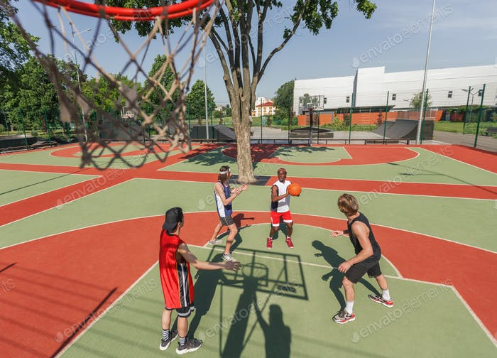 Above view of multiracial sports team playing basketball game at outdoor court