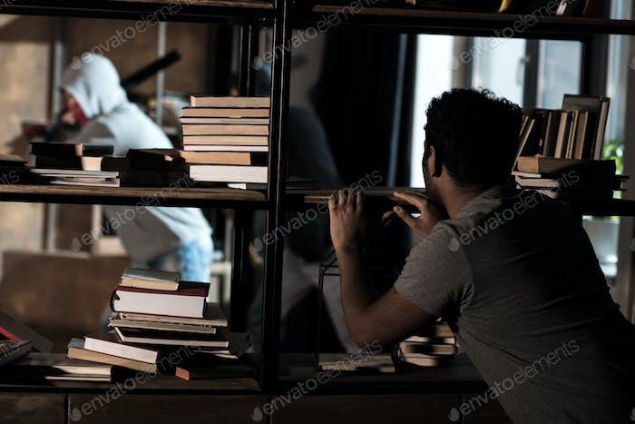 Scared man hiding from burglars behind bookshelves, house robbery scene