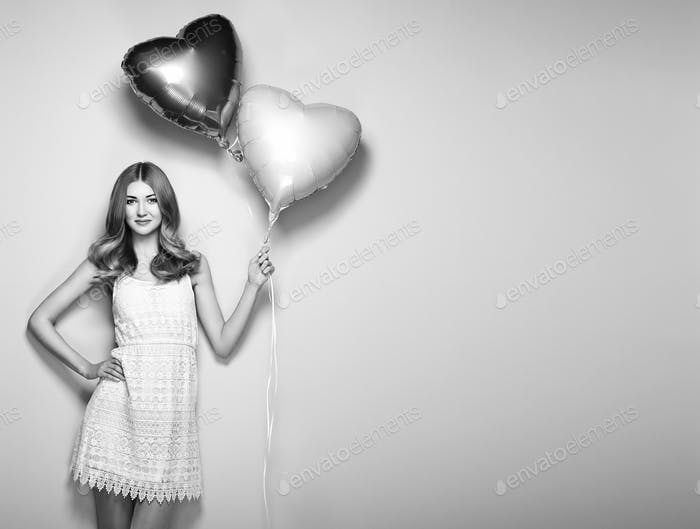 Beautiful young woman with heart shape air balloon