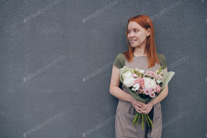 Smiling talented young female florist with red hair