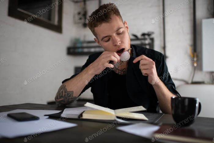 Pensive hipster man cleaning eyeglasses and preparing to study