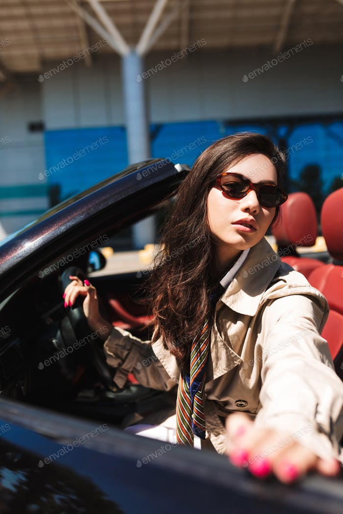 Young beautiful lady in sunglasses and trench coat opening cabri