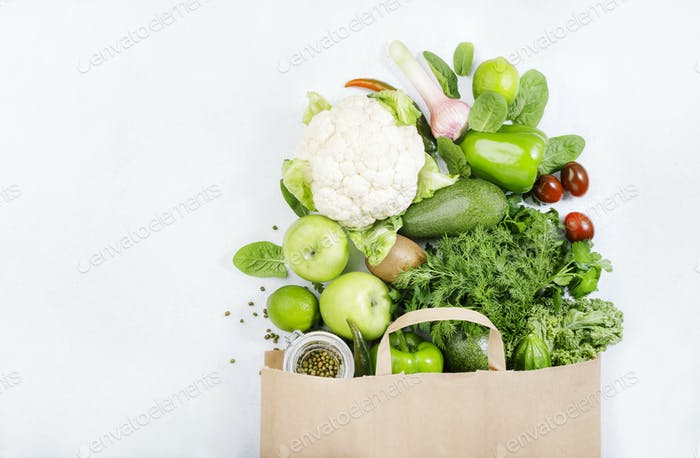 Healthy green vegan vegetarian food in full paper bag, vegetables and fruits