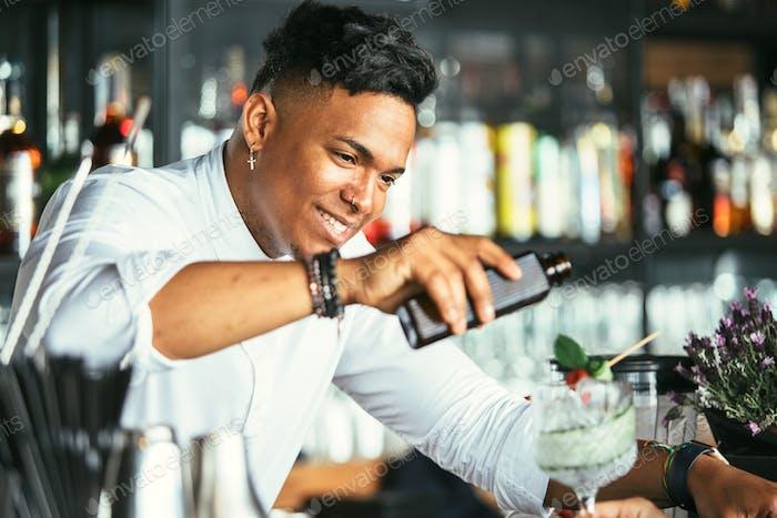 Smiling bartender serving cocktail