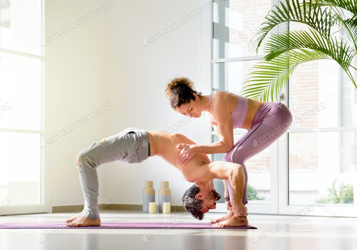 Female personal trainer assisting a man doing yoga