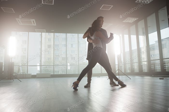 Kizomba dancers showing their passion for dancing kizomba in front a dancing room with big windows
