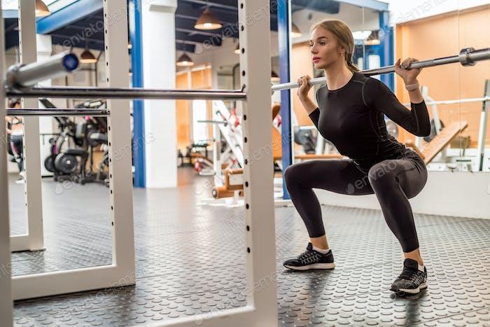 Junge Frau tut Langhantel Kniebeugen in modernen Fitness-Studio