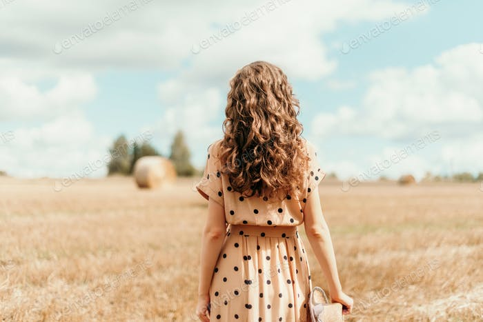 Woman in beige polka dot dress with curly hair, straw hat standing on harvested field with straw