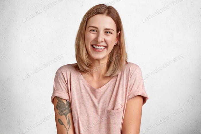 Happy European female laughs joyfully, shows white teeth, has bobbed hairstyle, dressed in casual t