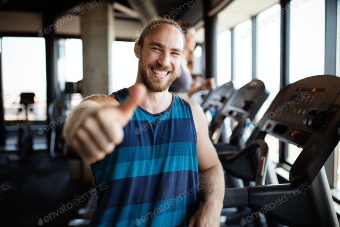 Portrait of happy man gesturing thumbs up at gym