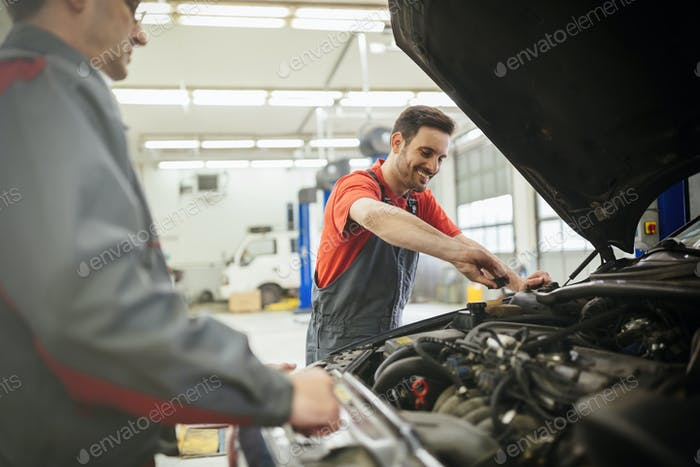Car mechanics working and maintaining car