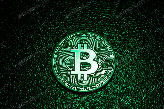 A coin with bitcoin logo in a green lighting.