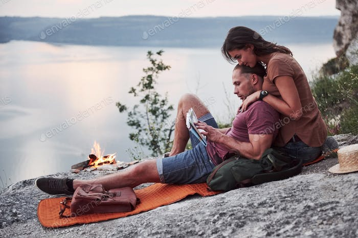 Couple with backpack sitting near the fire on top of mountain enjoying view coast a river or lake