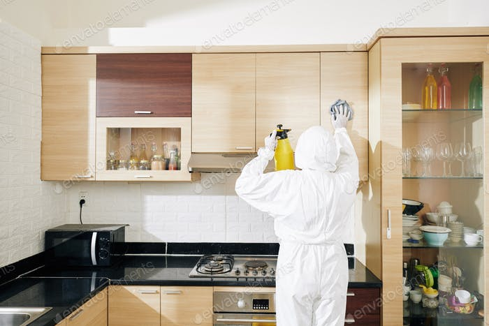 Worker wiping kitchen cabinets