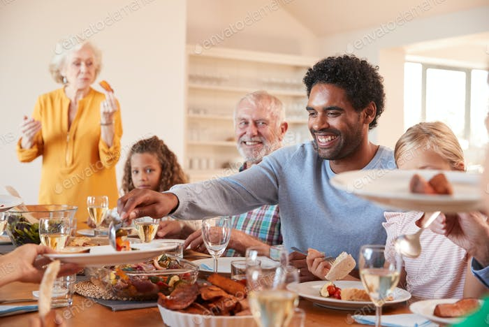 Father Serving Food As Multi-Generation Family Meet For Meal At Home