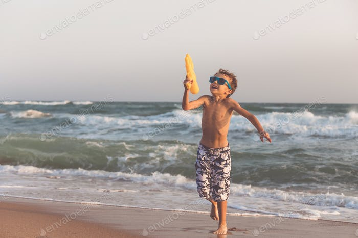 One happy little boy playing on the beach at the day time.