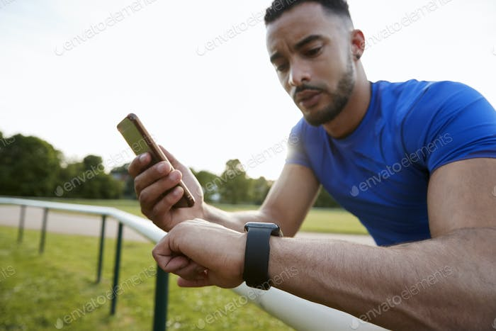 Male athlete using fitness app on smartphone and smartwatch