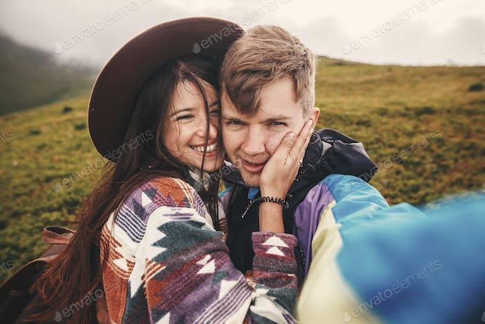 Happy hipster couple making selfie and smiling on top of  sunny  mountains