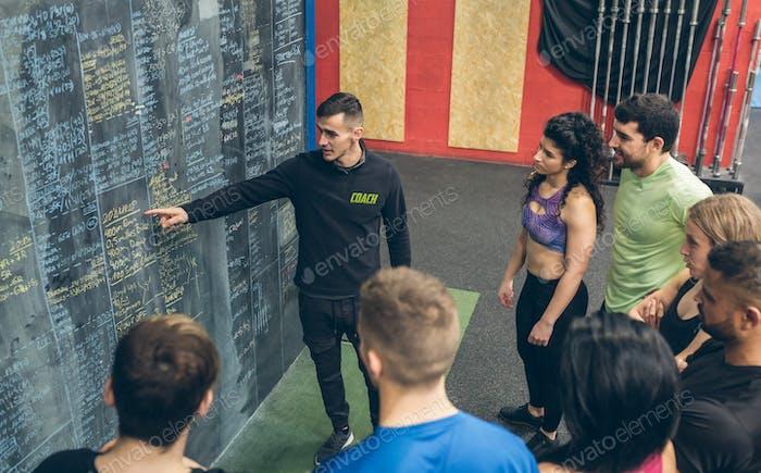 Coach explaining to athletes in the gym