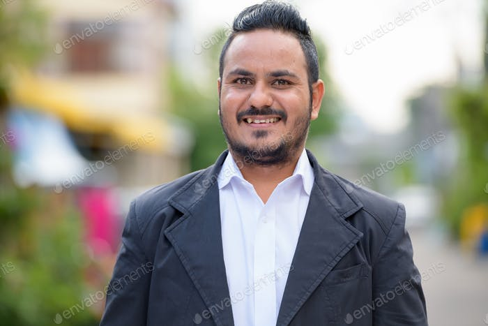 Face of happy bearded Indian businessman smiling outdoors