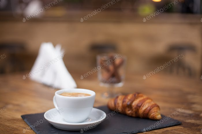 Cappuccino coffee in a white cup on a wooden table next to a delicious croissant