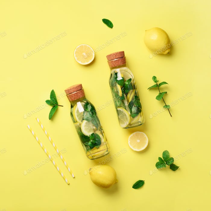 Bottle of detox water with mint, lemon on yellow background. Flat lay. Square crop. Citrus lemonade