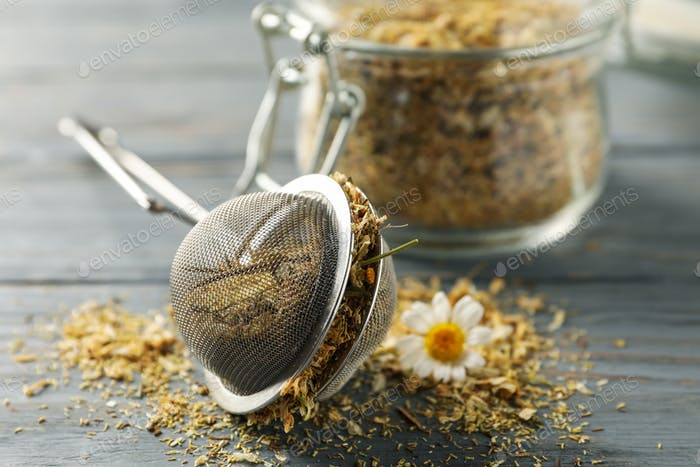 Glass jar and sieve with dried chamomile on gray wooden background