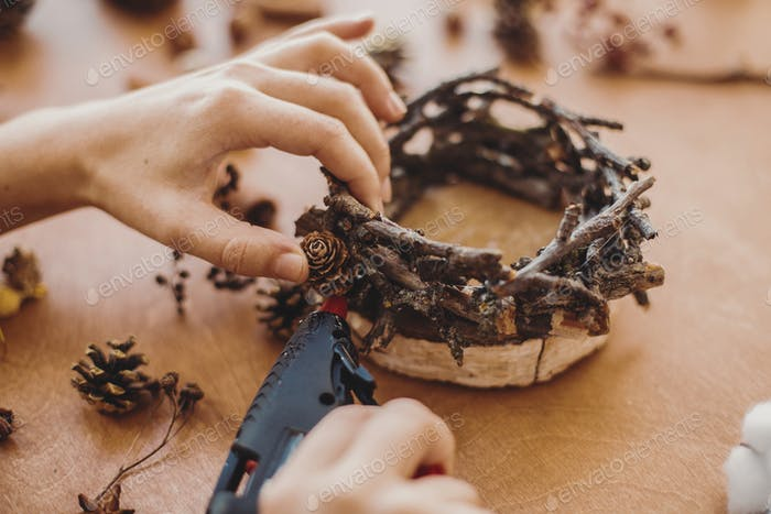 Hands holding glue gun and making rustic festive decoration