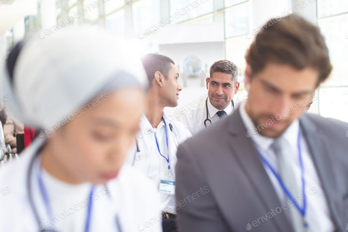 Front view of diverse male doctors interacting with each other during seminar in a conference room