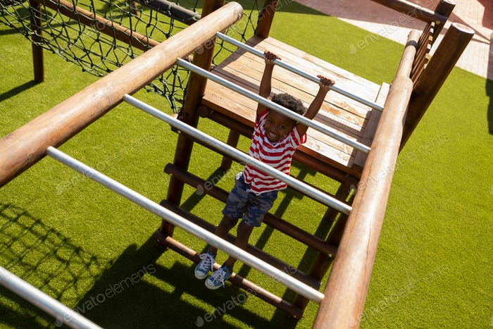 Cute schoolboy playing on horizontal ladder in the school playground on a sunny day