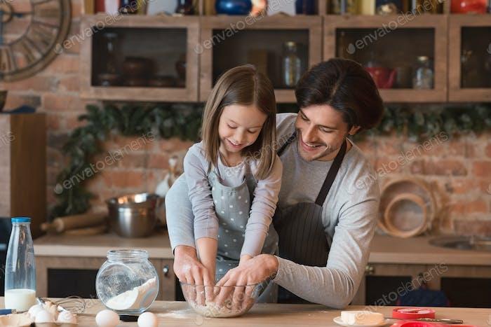 Junger Vater und seine süße kleine Tochter machen Teig zusammen in der Küche