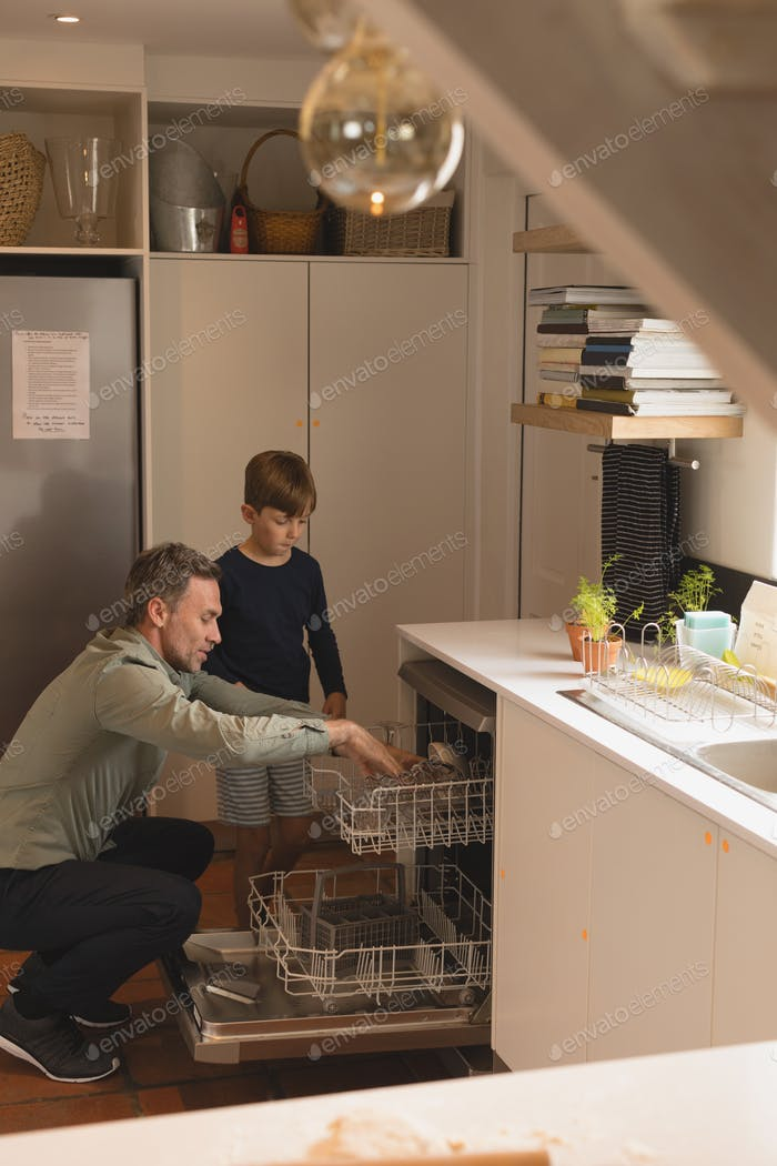 Side view of father and son putting utensils in dishwasher at home