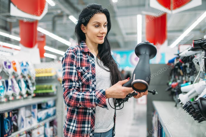 Young woman choosing hairdryer in supermarket