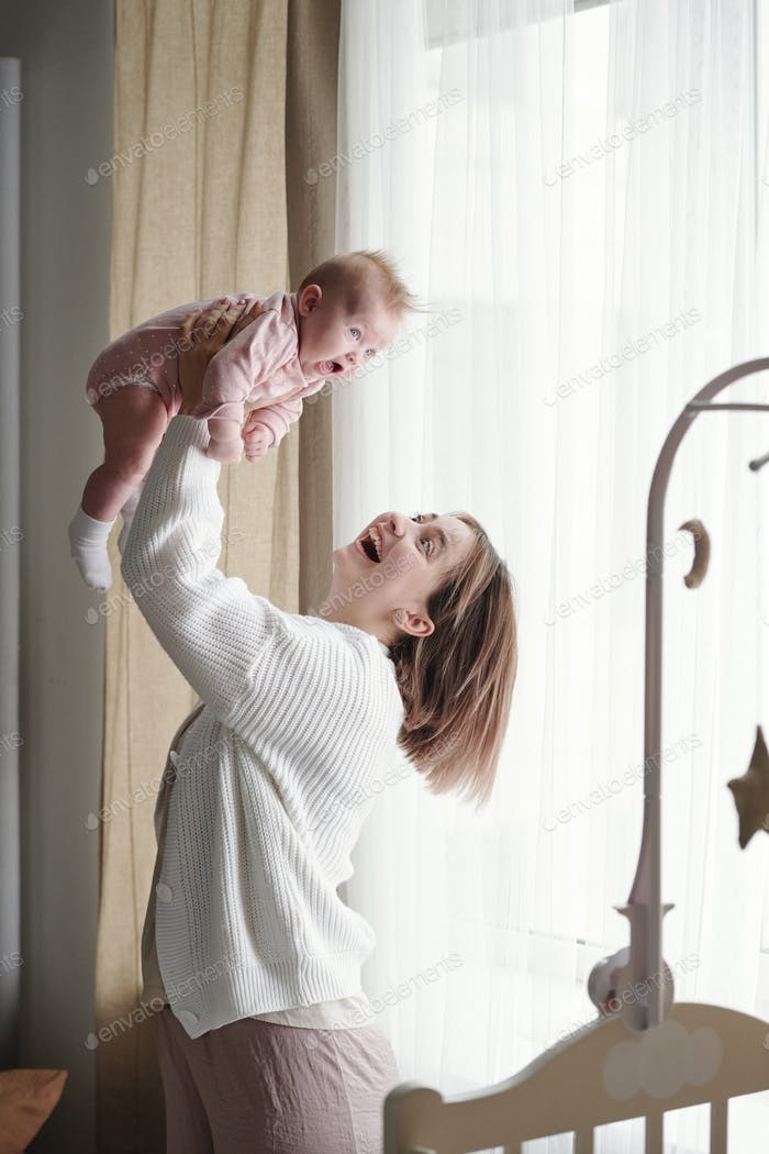 Cheerful young mother playing with her cute baby daughter