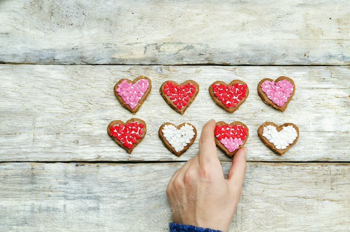 Male hands holding cookie in the forms of heart