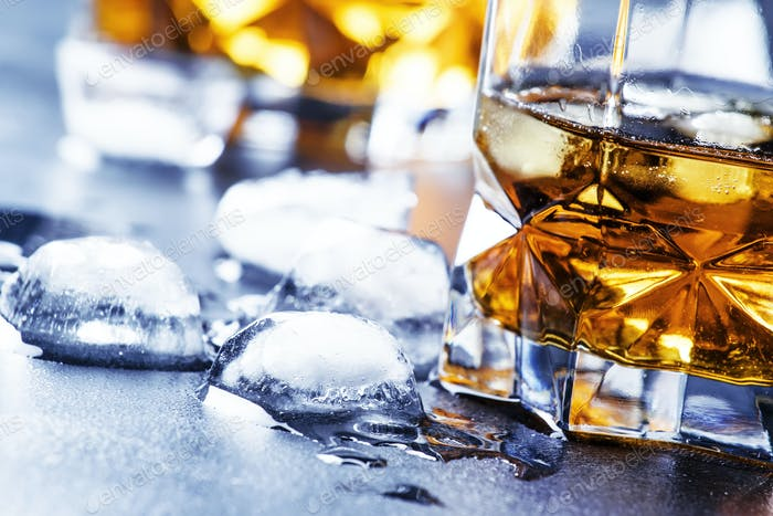 Cold whiskey with ice cubes in black table