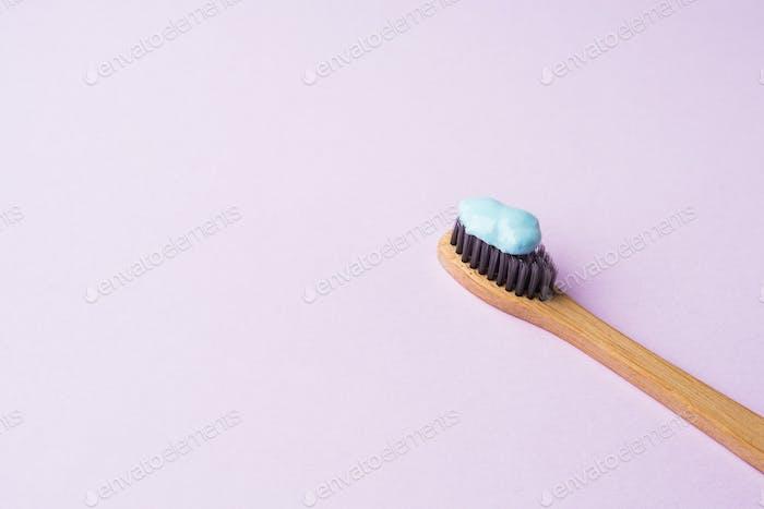 Bamboo toothbrush on pink pastel background