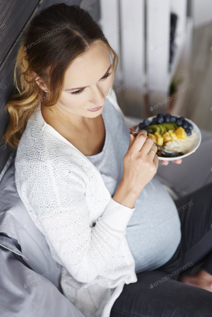 Pregnant woman having breakfast at bedroom