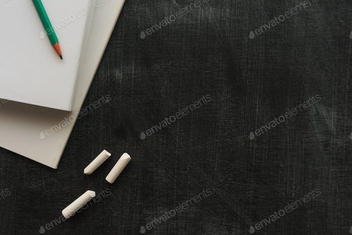Books, pencil and chalk on blackboard