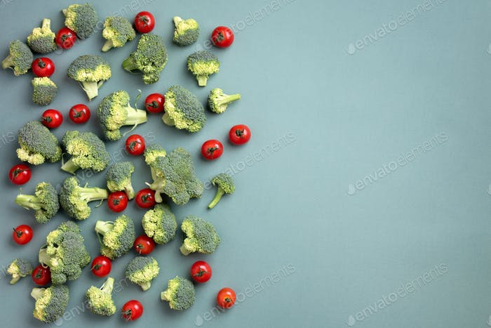 Creative layout of broccoli, tomatoes on green paper background. Top view. Food pattern in minimal