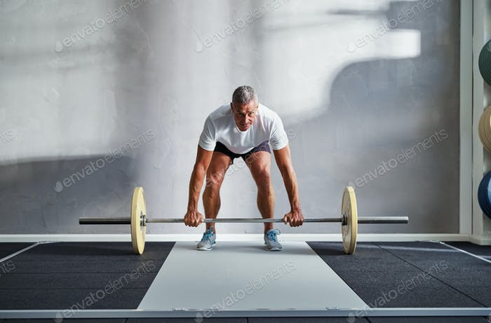 Fit senior man lifting weights alone in a gym