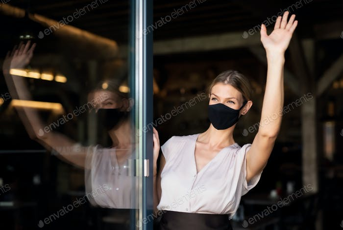 Portrait of waitress with face mask standing at the door in restaurant, waving