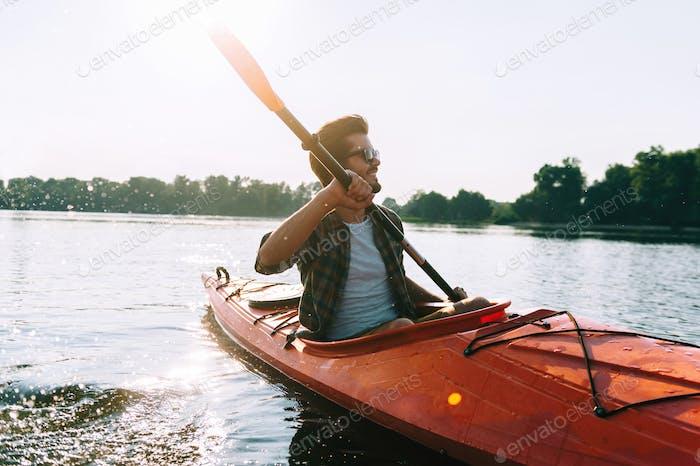 Mann-Kajak fahren. Schöner junger Mann beim Kajakfahren auf dem See und lächeln