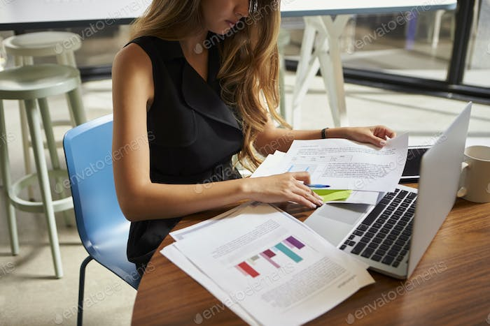 Businesswoman working on documents in office, close up, crop