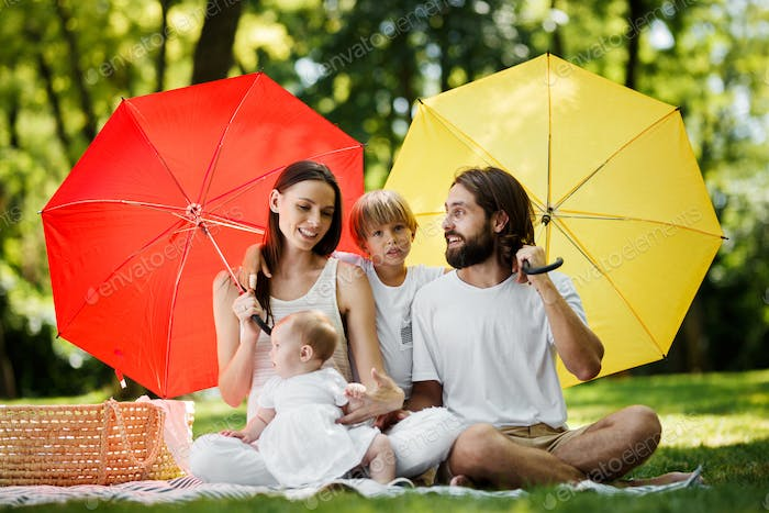 Funny kids with mom and dad sitting on the blanket under the big red and yellow umbrellas covering