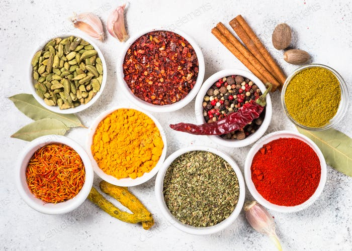 Colored indian spices on white table